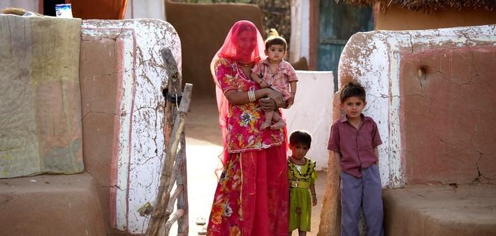 Femmes bishnoïs et ses enfants, devant leur maison.